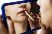 Žena maluje rty rtěnku před zrcadlem — Stock fotografie