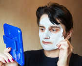 Beautiful woman takes beauty mask — Stock Photo