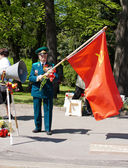 Old veteran with red flag on victory day — Stock Photo