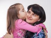 Girl kissing her mother — Stock Photo