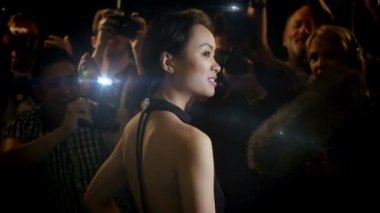 Model poses in front of flashing bulbs of paparazzi — Vídeo de Stock