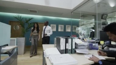 Businessman and businesswoman talking together as they walk around the office — Stock Video
