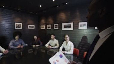 Business presentation with mature, experienced manager addressing his young team — Stock Video