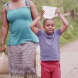 Young African boy and his mother carry containers of water back to their village — Stock Video