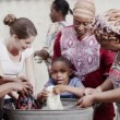 African family and community members work together, washing clothes by hand — Stock Video #44348195