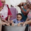 African family and community members work together, washing clothes by hand — Stock Video