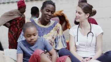 Medical worker from charity organisation chats with the mother of a young boy — Stock Video