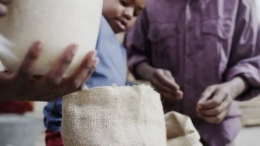 African father and son measuring out cups of rice or grain from a hessian sack — Stock Video