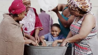 African family and community members work together, washing clothes by hand — Stock Video #44348213
