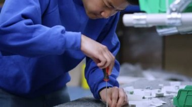 Young Asian factory worker concentrating on his work — Stock Video