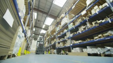 Forklift truck driver in a factory or warehouse driving between rows of shelving — Stock Video