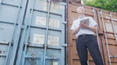 Businessman with digital tablet checking containers for shipping — Stock Video