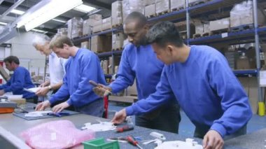 Male factory staff of mixed ethnicity working together on an assembly line — Stock Video