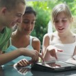 Young friends in the garden on a summer day playing with a computer tablet — Stock Video