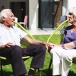 Retired couple sit and hold hands as they relax in the garden — Stock Video #44378305
