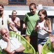 Grandfather plays a trick on his family as they sit in the garden at home — Stock Video #44379081