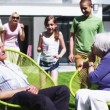 Grandfather plays a trick on his family as they sit in the garden at home — Stock Video #44379183