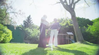 Romantic retired couple embrace and look out over their garden on a summer day — Stock Video