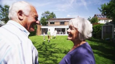 Loving senior couple embrace as they watch their family play in the garden — Stock Video