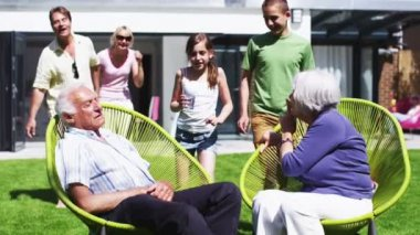 Grandfather plays a trick on his family as they sit in the garden at home — Stock Video