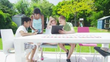 Jovens amigos no jardim em um dia de verão, jogando com um comprimido de computador — Vídeo stock