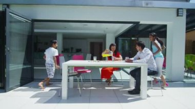 Happy asian family drinking juice on terrace of their modern home on a sunny day — Stock Video