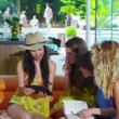 Happy group of female friends relaxing in modern home with a computer tablet — Stock Video