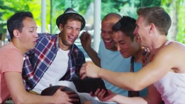 Happy group of male friends relaxing in modern home with a computer tablet — Stock Video