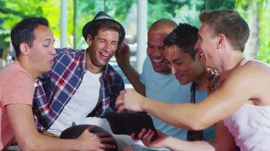 Feliz grupo de amigos do sexo masculino relaxantes em casa moderna com uma placa de computador — Vídeo stock