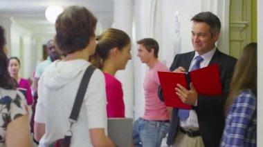 Teacher checking register as students enter classroom — 图库视频影像