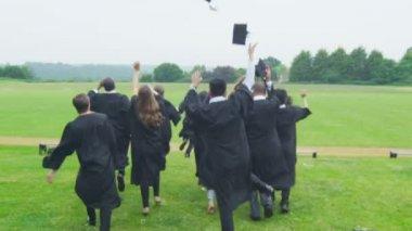 Students on graduation day run through landscape — Stock Video