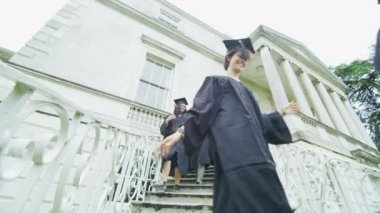 Students on graduation day run down staircase — Stock Video
