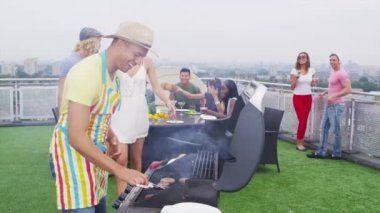 Friends enjoying a rooftop barbecue in the city — 图库视频影像