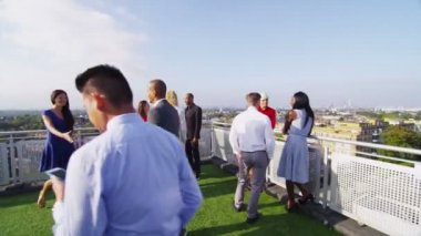 Group chatting on rooftop terrace — Stock Video
