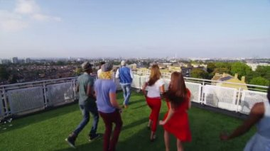 Friends on rooftop run out look at city — Stock Video