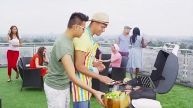 Friends enjoying a rooftop barbecue in the city — Stockvideo