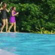 Friends enjoying drinks and dancing by pool — Stock Video #44727279