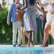 Friends enjoying drinks and dancing by pool — Stock Video #44727777
