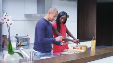 Couple preparing meal and following recipe on tablet — Wideo stockowe