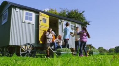 Family relaxing outside quaint caravan — Stock Video