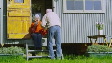 Senior couple relaxing outside quaint caravan — Stock Video