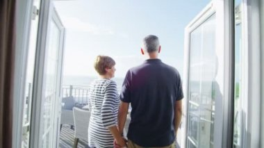 Mature couple go to look from balcony — Stock Video