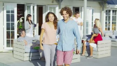 Couple socializing with friends outside beachside home — Stock Video