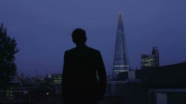 Erfolgreicher geschäftsmann blickt auf den blick auf die skyline von london in der nacht — Stockvideo