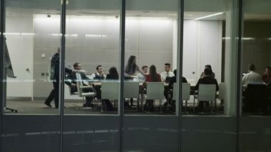 Diverse business team in late night boardroom meeting in contemporary office — Stock Video