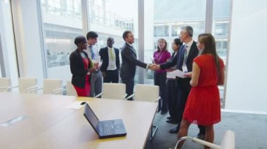 Diverse business team shake hands at the end of a boardroom meeting — Stock Video