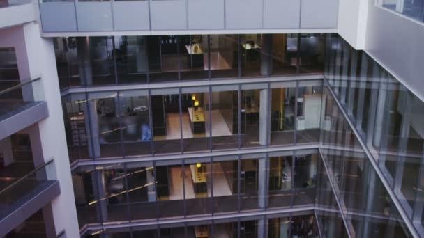 Vue intérieure de l'immeuble moderne avec cloisons en verre et atrium central — Vidéo