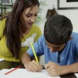 A mother sits beside her son, helping him to draw and write — Stock Video #45205307