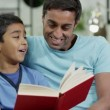 Father and son spending time together at home, reading a book — Stock Video