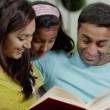 Mother, father and daughter reading a book together at home — Wideo stockowe #45205671